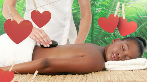 Masseuse placing hot massage stones on the back of a black female at spa for valentine day 4k Animation