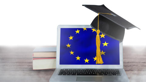 European flag waving on the screen of a laptop, with books hat and a wooden table Animation