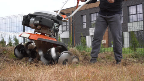 Gardener loosens soil with walking tractor in urban flower beds. Gimbal movement Live Action