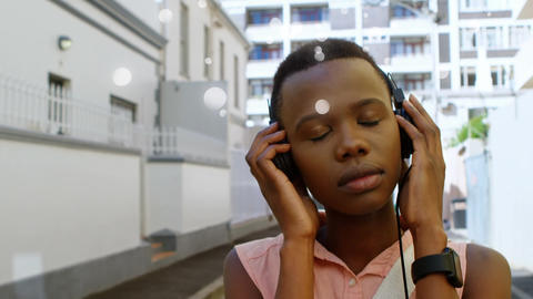 Beautiful African-american listening music with headphone on street in the city Animation