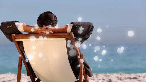 caucasian man sitting on deck chair in front of sea with bubble light animation Animation