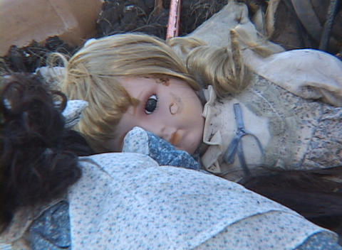 A child's doll lies in the rubble of a house after... Stock Video Footage