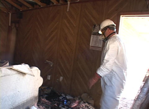 A worker clears debris from a home damaged by Hurricane Katrina Footage