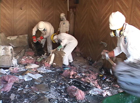 Workers clear debris from a Hurricane Katrina damaged home Stock Video Footage
