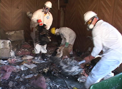 Workers clear debris from a Hurricane Katrina damaged home Footage