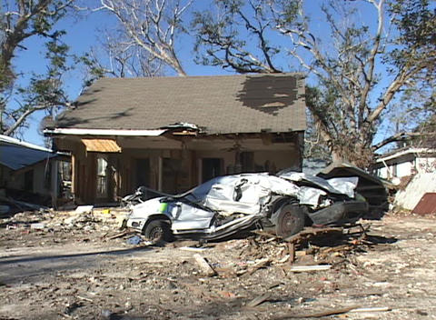 A crushed car in front of a home shows the destruction caused by Hurricane Katrina Footage