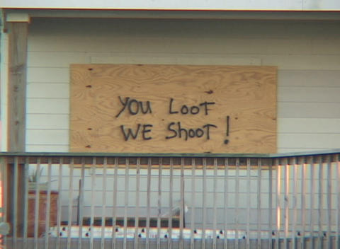 Medium shot of a boarded up house warning looters not to... Stock Video Footage
