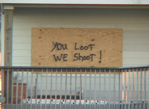 Medium shot of a boarded up house warning looters not to enter after Hurricane Katrina Footage