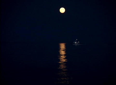 A fishing boat heads out to sea under the moonlight Stock Video Footage