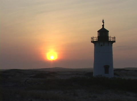 The Race Point Lighthouse silhouettes the horizon during golden-hour Footage