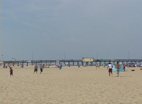 Medium shot of a summer beach scene at Atlantic City, New Jersey with amusement park in background Footage
