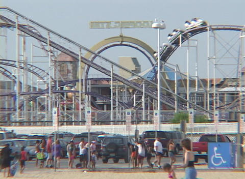 Medium-shot of people enjoying a day at a beachside amusement park Footage