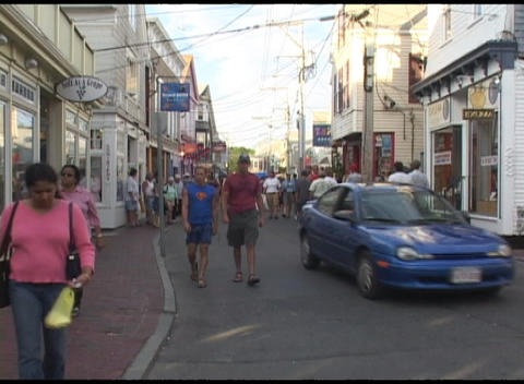 Medium-shot of tourists walking through an all-American town in New England Footage