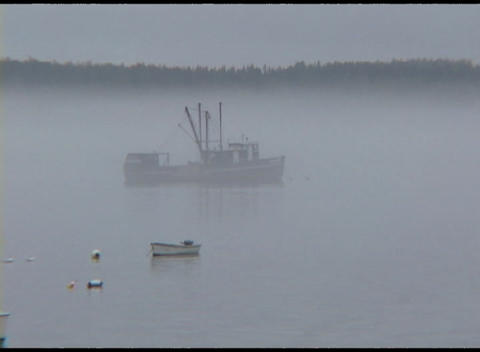 Medium shot of fishing boats sitting in a foggy harbor in Jonesport, Maine Footage