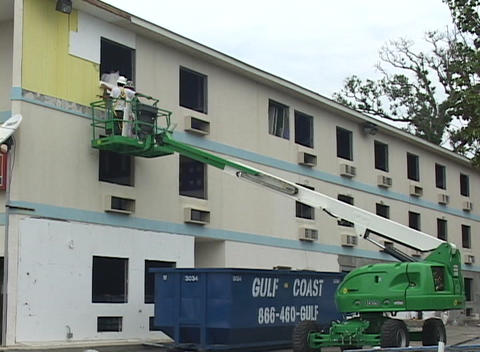 Construction workers use a crane to restore damaged buildings following Hurricane Katrina Footage