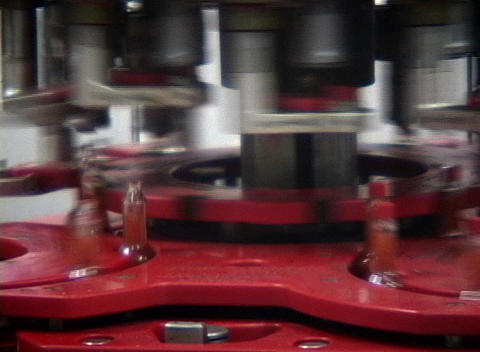 Bottles of hot sauce spin on an assembly machine in a... Stock Video Footage