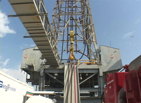 An oil derrick stands in the sun Footage
