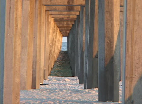 Pier pillars extend from a sandy shore to the ocean Stock Video Footage