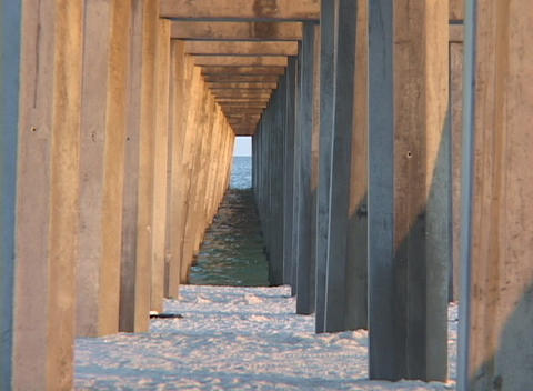 Pier pillars extend from a sandy shore to the ocean Footage