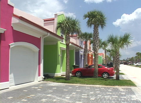 A car sits in a driveway in front of a green beach house Stock Video Footage