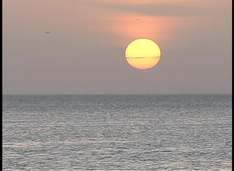 The sun hovers over calm water during golden hour Footage