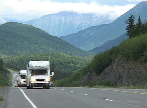 Motor homes move down a road Stock Video Footage