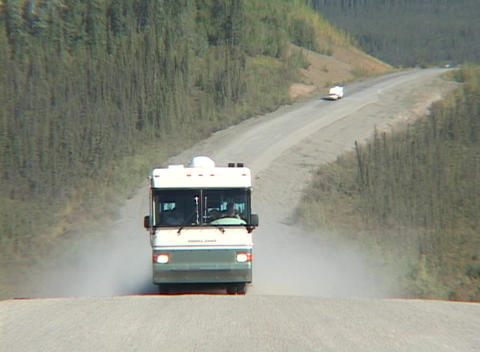 A motor home travels down a dirt road in Alaska Footage