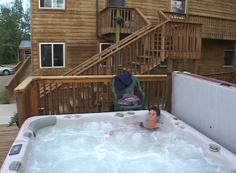 A woman relaxes in a large hot tub Stock Video Footage