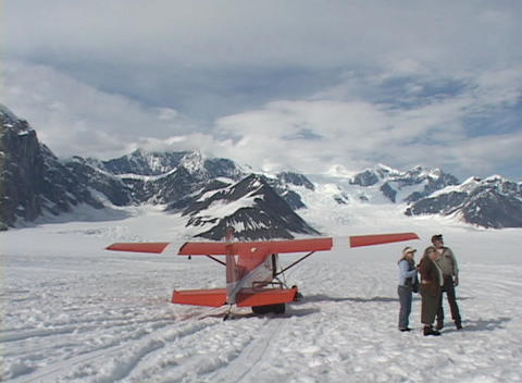 Tourists mill around a ski plane after it has landed on a... Stock Video Footage