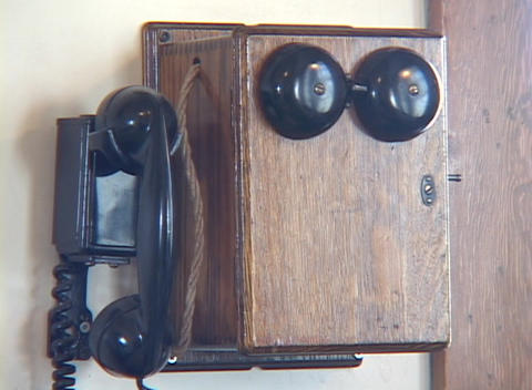 An old fashioned telephone hangs on a wall Stock Video Footage
