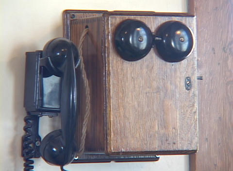An old fashioned telephone hangs on a wall Footage