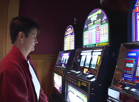 A woman plays a slot machine in a casino Stock Video Footage