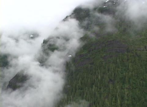 A small plane flies through clouds in a remote part of Alaska Footage