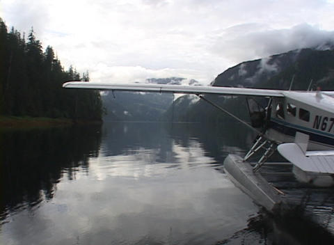 A float plane taxis away from the dock in this beautiful Alaska shot Footage