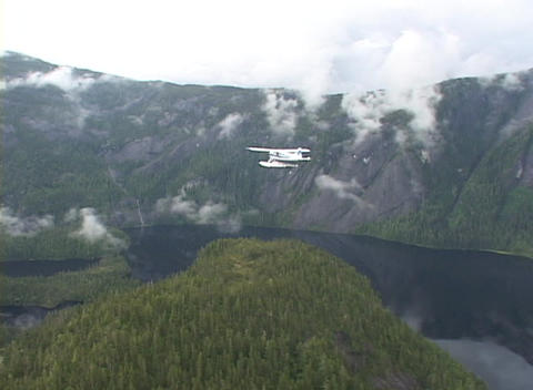 An aerial of a float plane flying over Alaskan fjords Footage