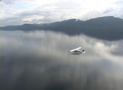 An aerial of a float plane flying over Alaskan fjords Stock Video Footage