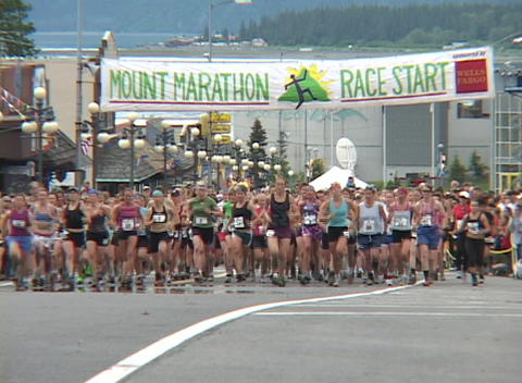 Runners leave the starting line in a marathon and running towards the camera Footage