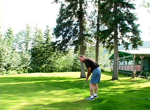A golfer putts the ball while the camera zooms into a... Stock Video Footage