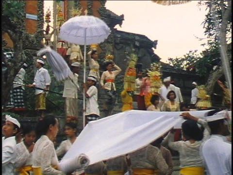 A religious procession walks to a temple in Bali Stock Video Footage