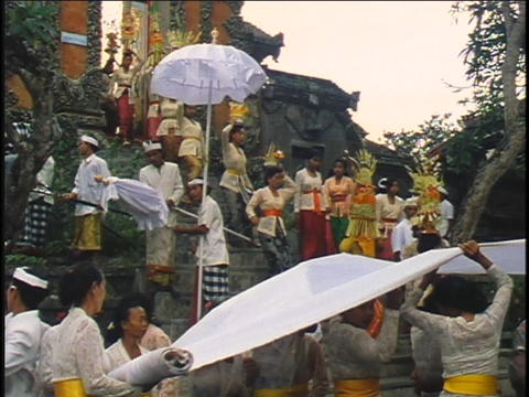 A religious procession walks to a temple in Bali Footage