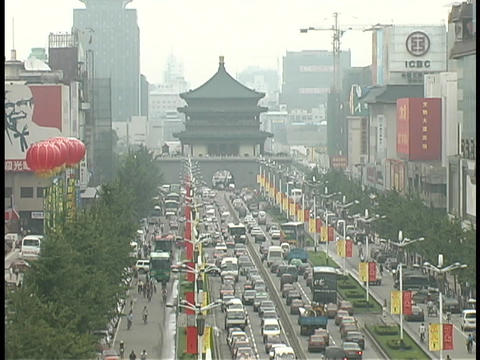 Traffic drives along a busy, flag lined street in Xian Footage
