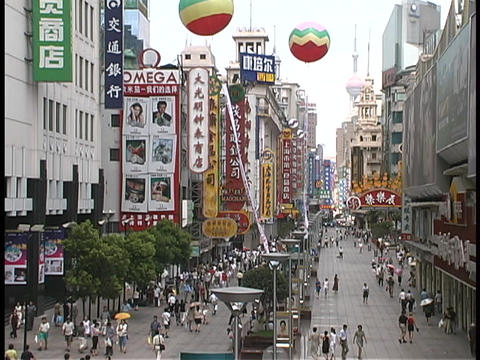 Businesses and pedestrians fill a shopping district in Shanghai, China Footage