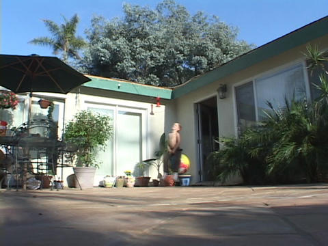 A small boy rides on a bouncy ball across a patio Stock Video Footage