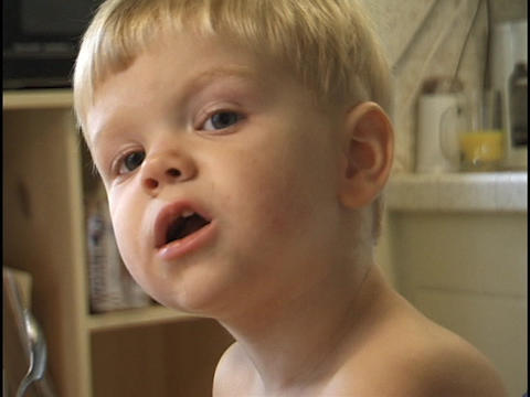 A young toddler stretches to look around the camera while... Stock Video Footage