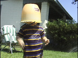 A child covers his head with a bucket, while playing in the water Footage