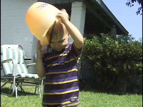 A child covers his head with a bucket, while playing in... Stock Video Footage