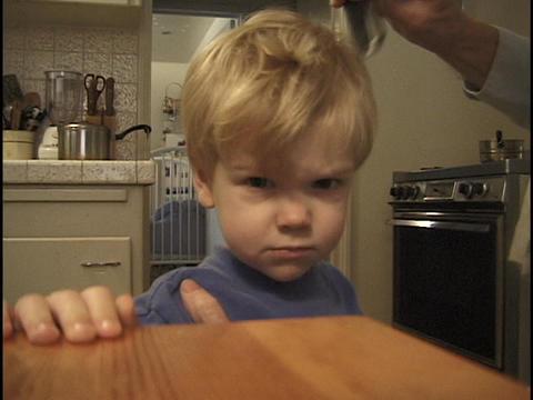 A parent combs a little boy's hair Footage