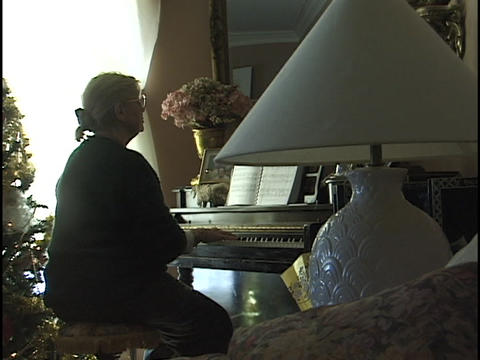 A woman plays a piano in a living room Footage