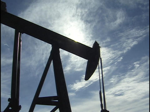 The sun silhouettes an oil well pumping in a Texas, oil... Stock Video Footage
