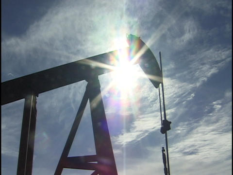 The sun silhouettes an oil well pumping in a Texas, oil field Footage